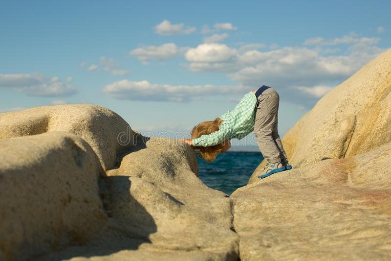 Yoga. Children yoga. Sports training for children in nature. Sea and sport. White stones on the shore. Cute kid on sea stock photography