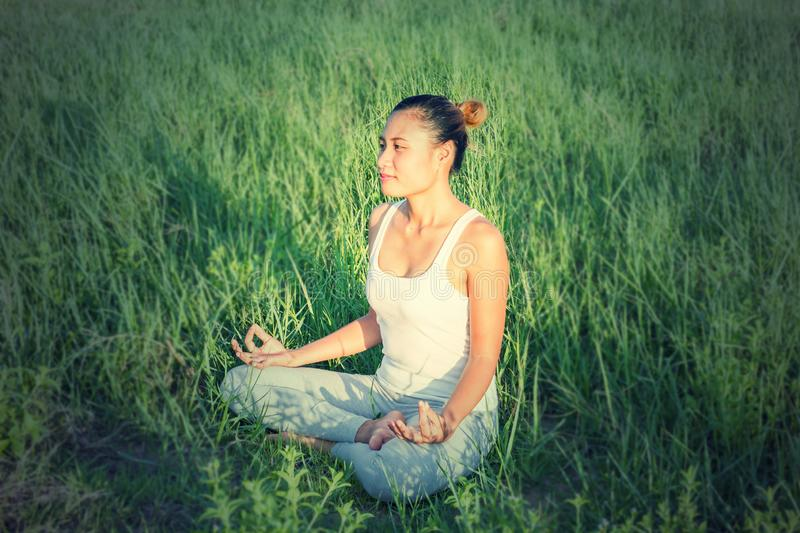 Yoga in the city: beautiful young fit woman wearing sportswear meditating, breathing, sitting with crossed legs in Half Lotus royalty free stock photos