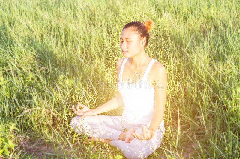 Yoga in the city: beautiful young fit woman wearing sportswear meditating, breathing, sitting with crossed legs in Half Lotus stock photo