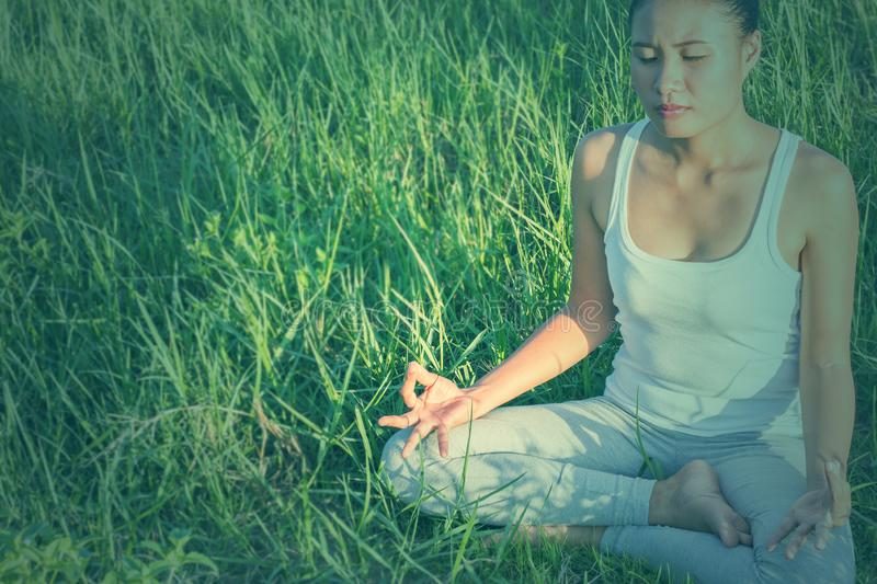 Yoga in the city: beautiful young fit woman wearing sportswear meditating, breathing, sitting with crossed legs in Half Lotus stock photos