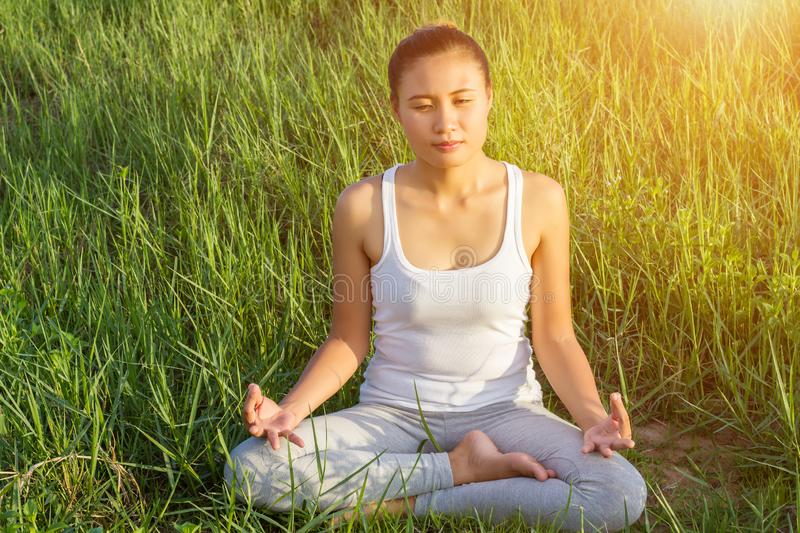 Yoga in the city: beautiful young fit woman wearing sportswear meditating, breathing, sitting with crossed legs in Half Lotus stock image