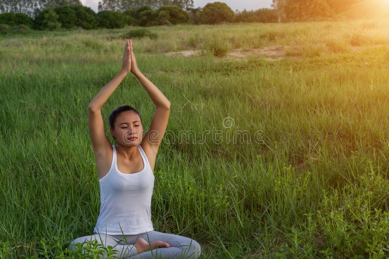 Yoga in the city: beautiful young fit woman wearing sportswear meditating, breathing, sitting with crossed legs in Half Lotus royalty free stock photography