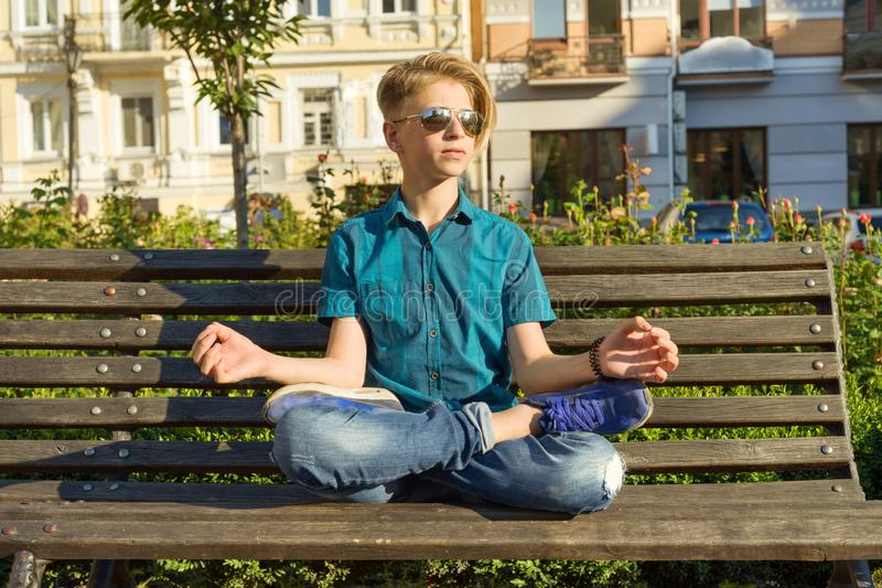 Yoga in city, teenage boy sits in lotus pose on bench in city park. Relax, rest, meditation royalty free stock photos