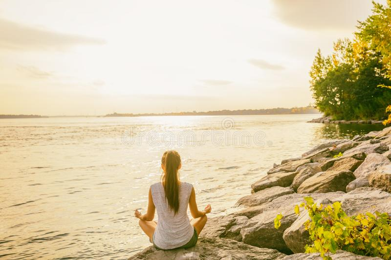 Yoga class outside in nature park by lake river shore. Woman sitting in lotus pose meditating by the water in morning sun flare royalty free stock images