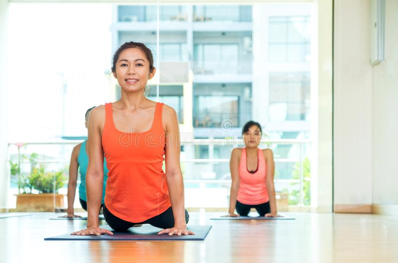 Yoga class in studio room,Group of people doing upward dog poses. Stretching pose,Wellness and Healthy Lifestyle royalty free stock image