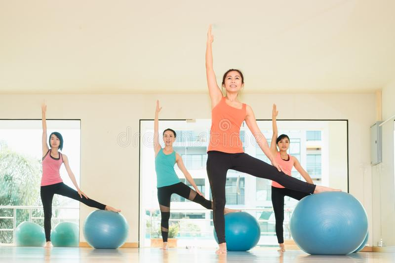 Yoga class in studio room,Group of people doing yoga pose with t. Raining ball, stretching pose,Wellness and Healthy Lifestyle royalty free stock photo