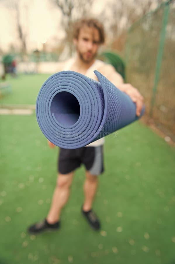 Yoga, couleur bleue de tapis de forme physique dans des mains d'homme musculaire images libres de droits