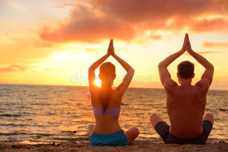 Yoga couple relaxing doing meditation on beach. Silhouettes of men and women people practicing yoga pose sitting at a beach in the lotus position with their royalty free stock images