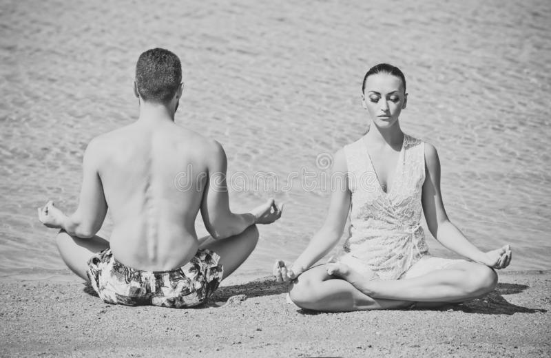 Yoga couple relaxing doing meditation on beach. Men and women people sitting in the lotus position at water royalty free stock photos