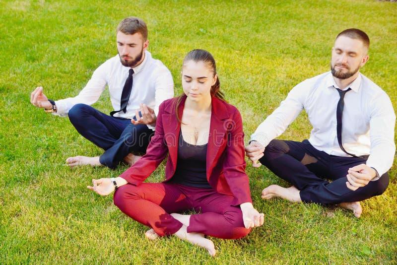 Yoga de bureau Trois jeunes employés dans une pose de lotus reposent o images stock
