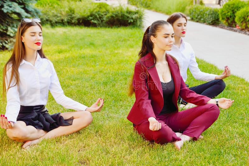 Yoga de bureau Trois jeunes filles dans une pose de lotus s'asseyent sur le GR images libres de droits