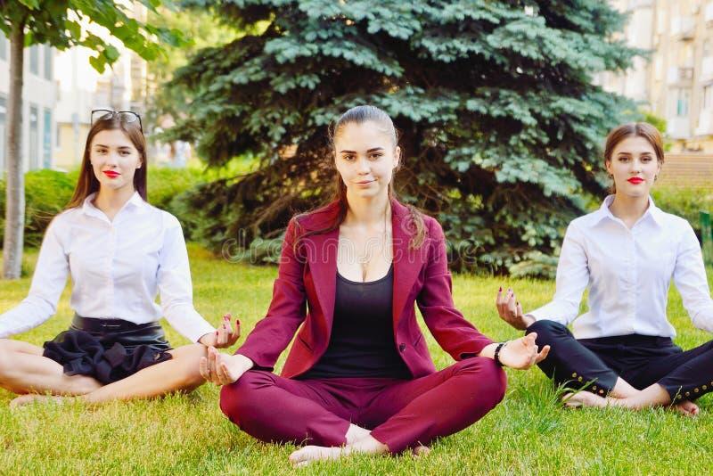 Yoga de bureau Trois jeunes filles dans une pose de lotus s'asseyent sur le GR image stock