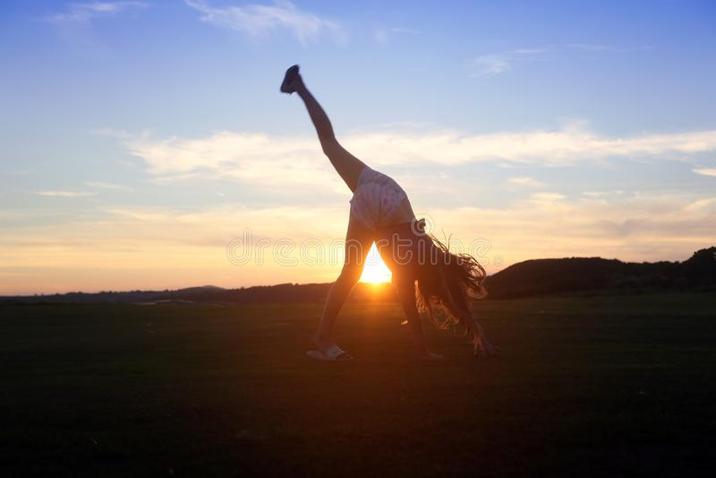 Yoga de essai de jeune fille au coucher du soleil dehors photographie stock