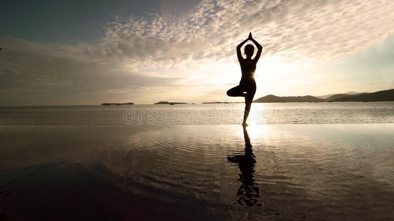 Yoga de exercice de touristes femelle sur la plage photo stock