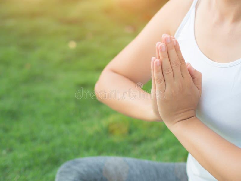 Yoga de femme de plan rapproché avec des mains de lotus à l'arrière-plan mol de foyer photographie stock libre de droits