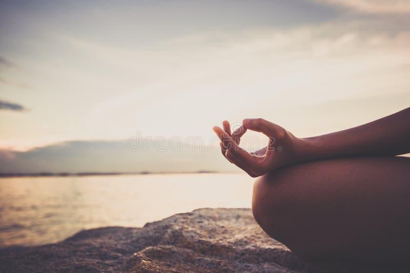 Yoga de femmes sur la roche près de la mer avec le ciel de coucher du soleil photo libre de droits
