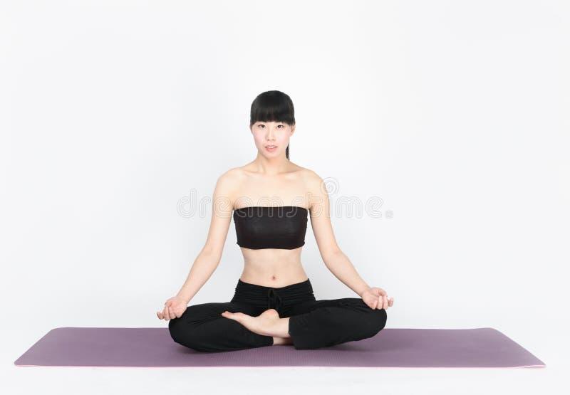 Yoga de formation de jeune femme sur le fond blanc photographie stock