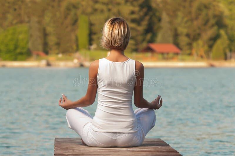 Yoga de jeune femme sur le lac photo stock