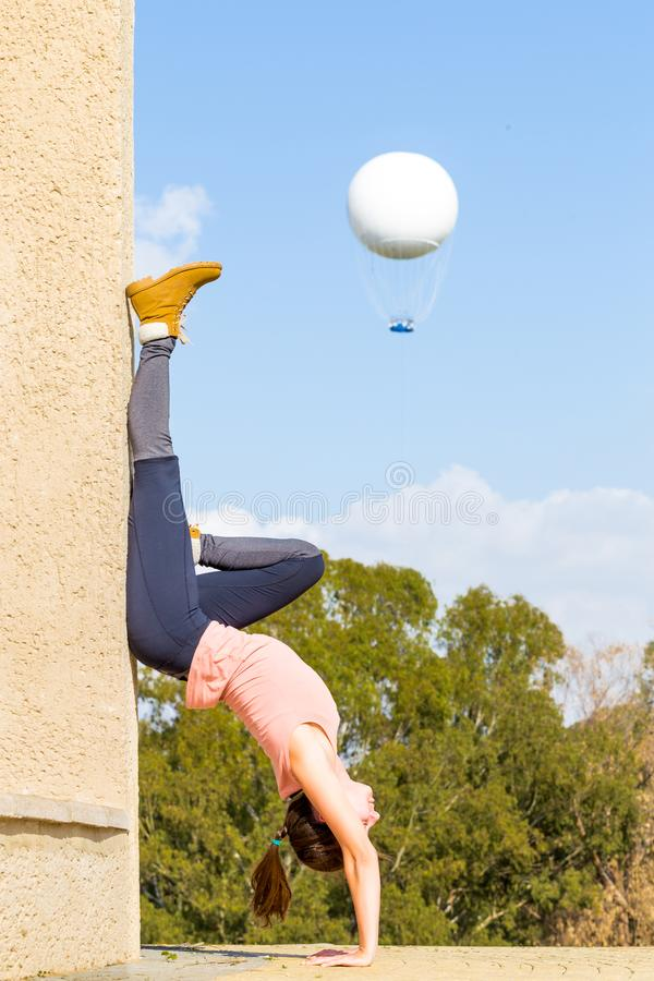 Yoga de la muchacha de la mujer joven de la posición del pino que entrena al globo del aire caliente imagenes de archivo