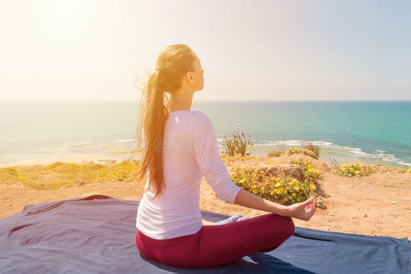 Yoga de la mujer joven en la playa del mar imagen de archivo