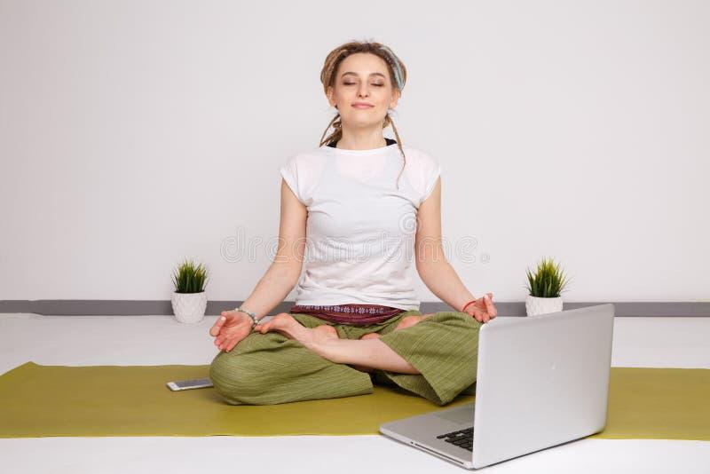 Yoga de la mujer que hace actitud del loto en la estera verde del yhe en el piso imagen de archivo libre de regalías