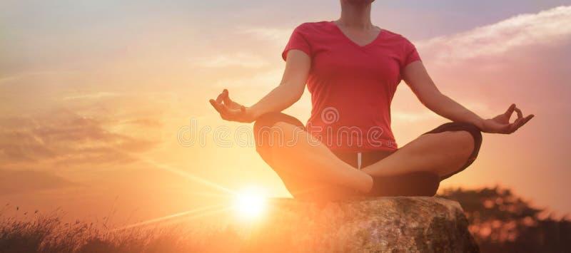Yoga de la mujer que practica y que medita en el parque y al aire libre en fondo del verano foto de archivo