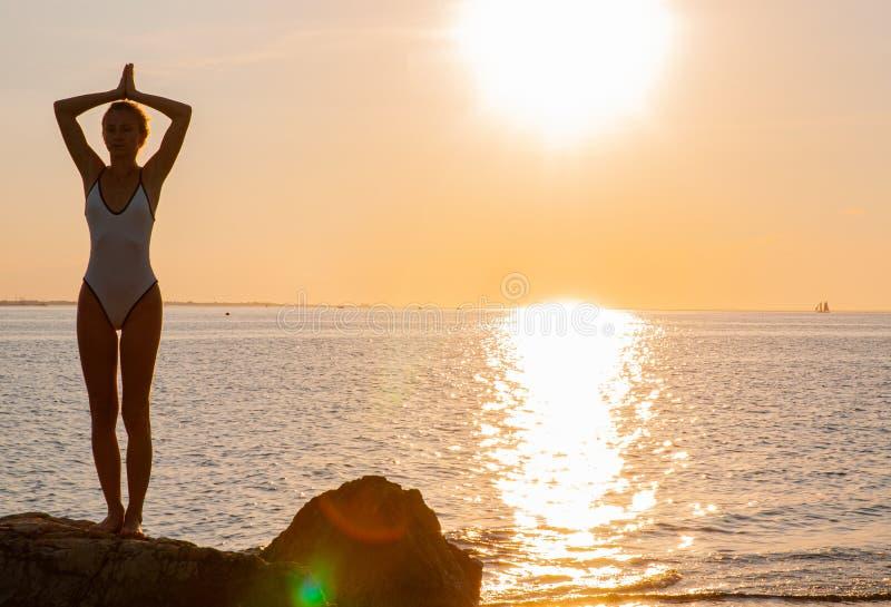 Yoga de la mujer de la silueta en la playa en la salida del sol La mujer está practicando yoga en la puesta del sol en orilla de  imagen de archivo