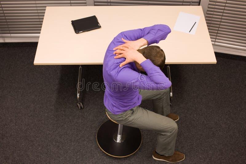Yoga de la oficina - hombre de negocios que ejercita en el escritorio foto de archivo libre de regalías