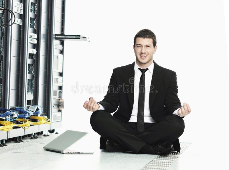 Yoga de la práctica del hombre de negocios en el sitio de servidor de red foto de archivo