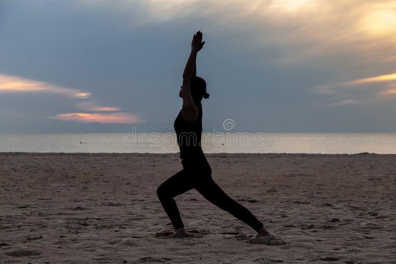Yoga de la práctica en la playa en madrugada fotografía de archivo