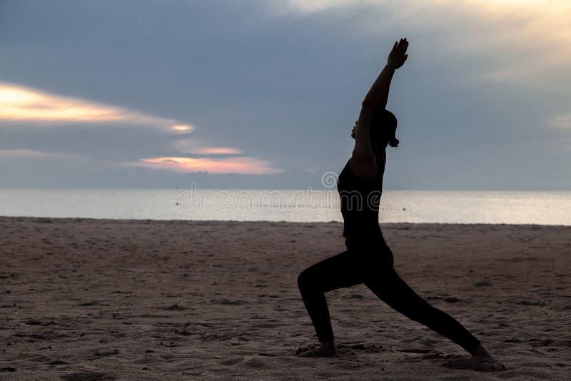 Yoga de la práctica en la playa en madrugada foto de archivo libre de regalías