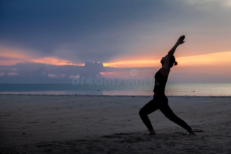 Yoga de la práctica en la playa en madrugada imagen de archivo libre de regalías
