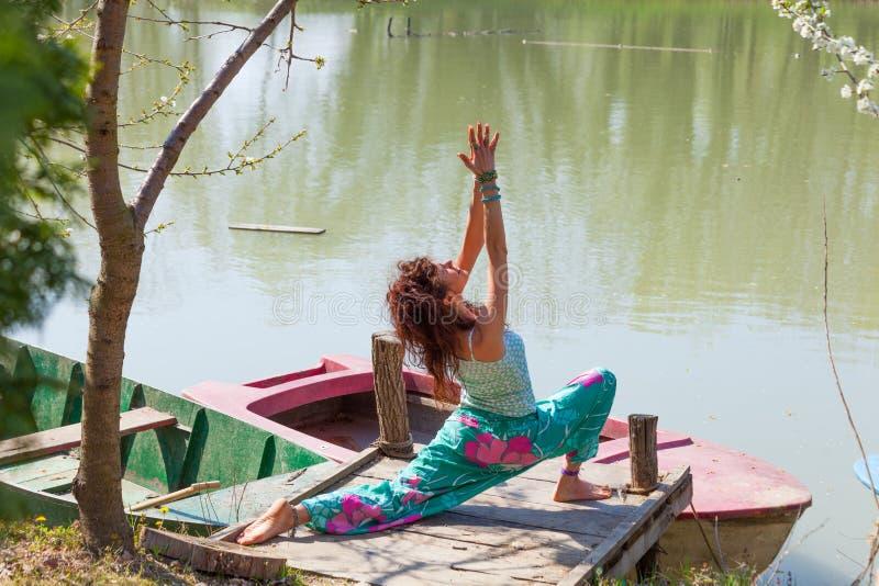Yoga de la práctica de la mujer joven al aire libre por el día sano del sumer del concepto de la forma de vida del lago fotos de archivo libres de regalías