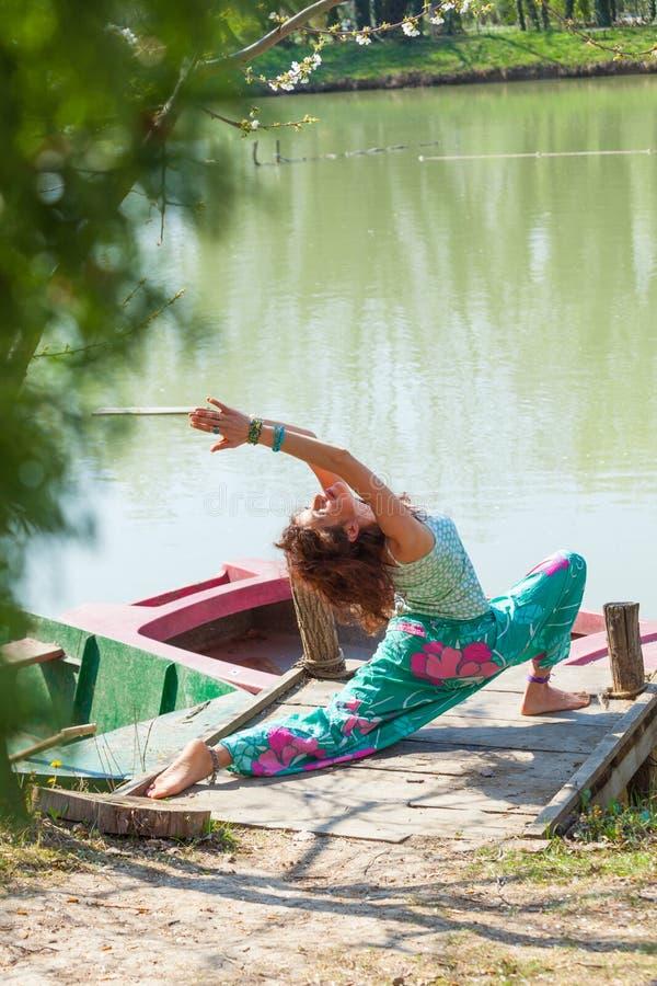 Yoga de la práctica de la mujer joven al aire libre por el tiro lleno del cuerpo de la forma de vida del lago del concepto del dí imagen de archivo libre de regalías