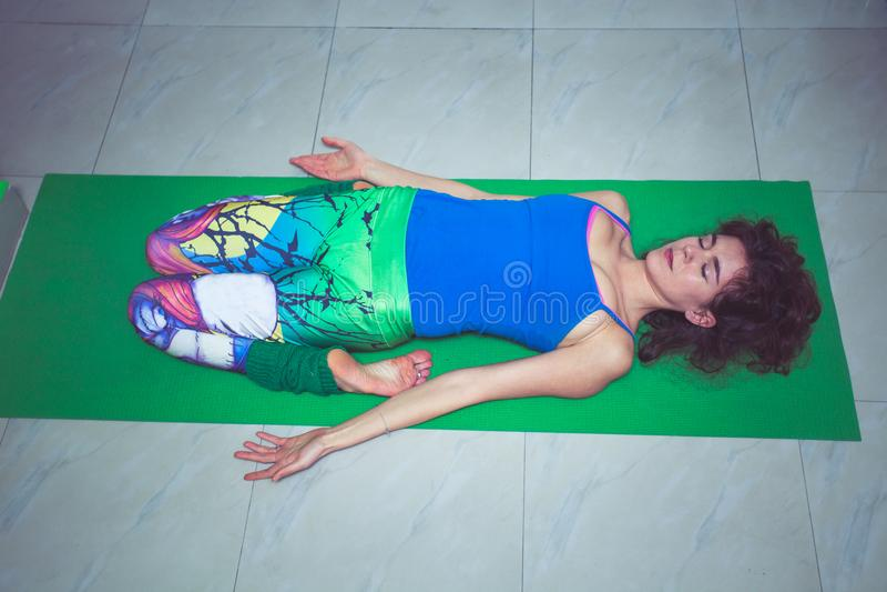 Yoga de la práctica de la mujer joven que miente en indoo de descanso de la posición del héroe fotografía de archivo