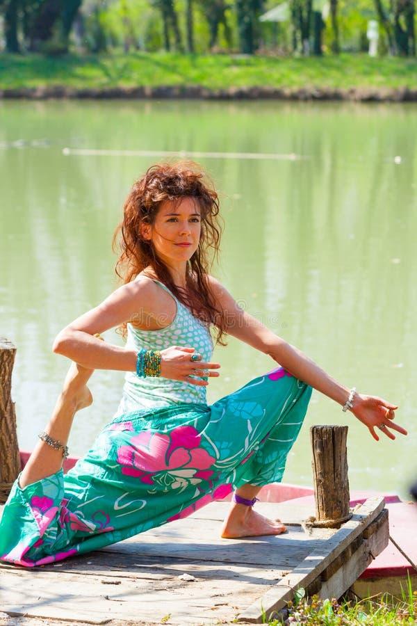Yoga de la pr?ctica de la mujer joven al aire libre por el concepto sano de la forma de vida del lago foto de archivo