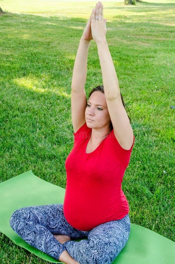 Yoga de maternidad, mujer joven que se sienta en la posición del rezo fotos de archivo