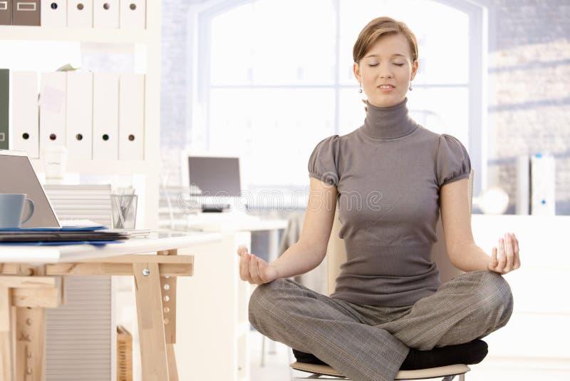Yoga de pratique attrayant d'employé de bureau photographie stock