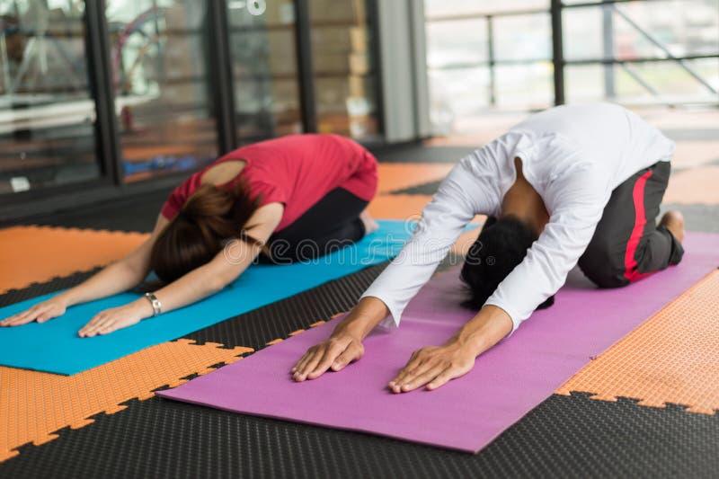 Yoga de pratique d'homme et de femme et étirage sur le tapis au centre de fitness ou au gymnase images libres de droits