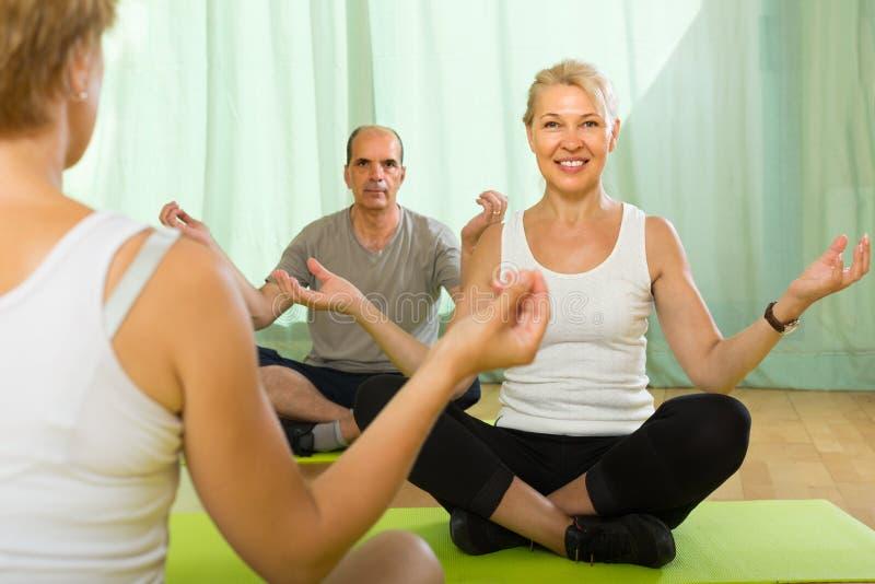 Yoga de pratique de couples mûrs avec l'instructeur photo libre de droits