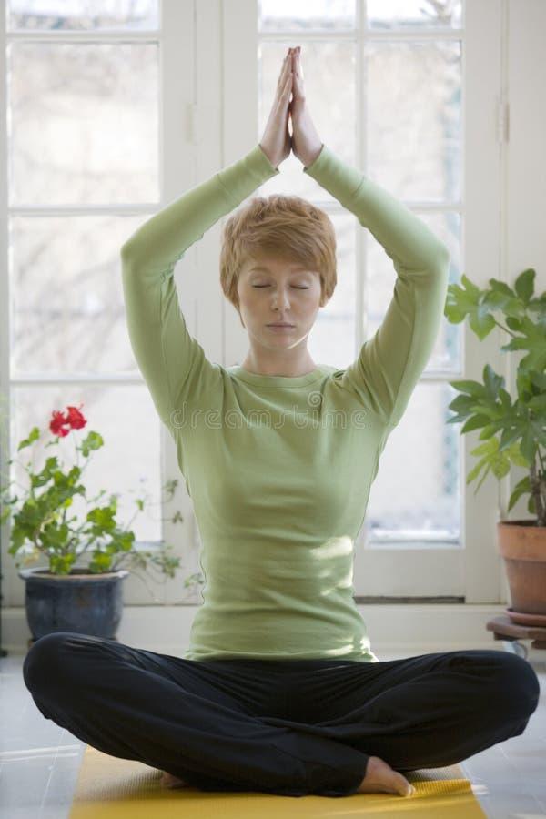 Yoga de pratique de femme assez jeune image stock