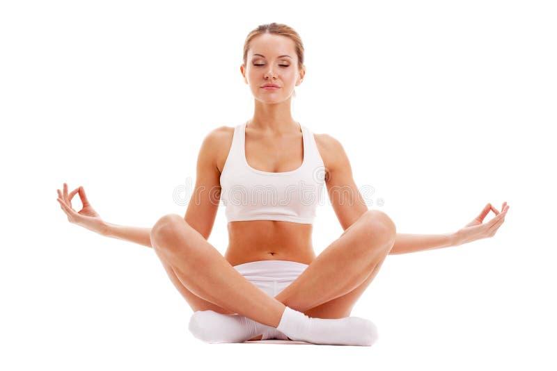 Yoga de pratique de femme dans la pose de lotus photo libre de droits