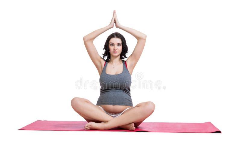 Yoga de pratique de femme enceinte et méditer photographie stock libre de droits