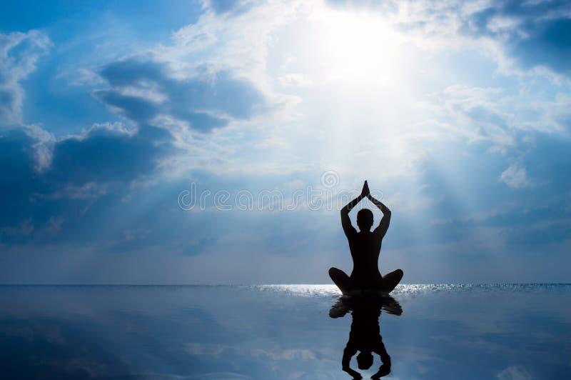 Yoga de pratique de femme, silhouette sur la plage au coucher du soleil image libre de droits