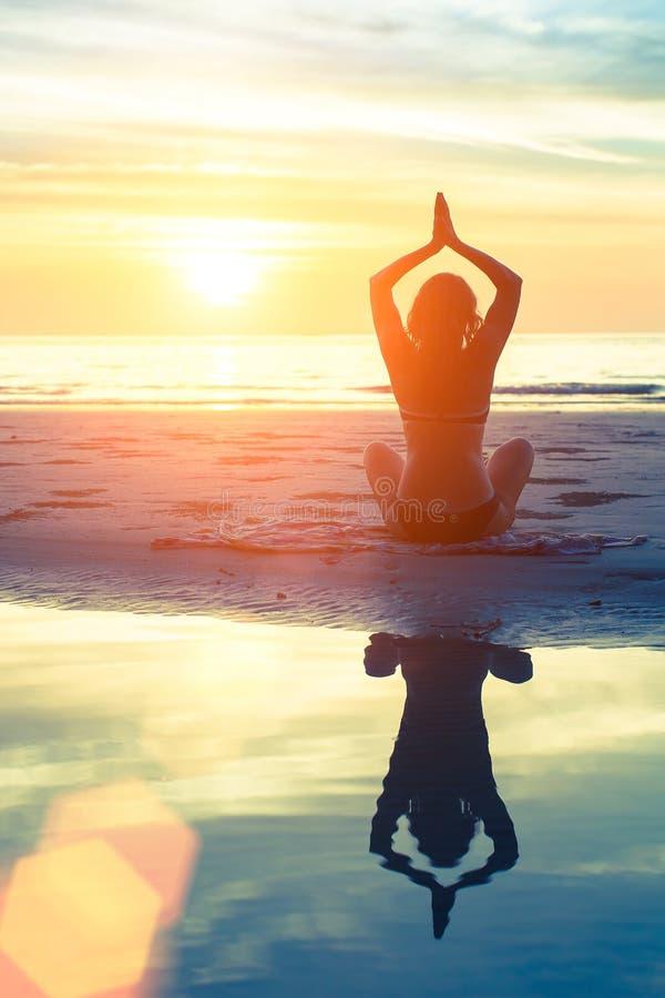 yoga de pratique de femme sur la plage au coucher du soleil étonnant photographie stock