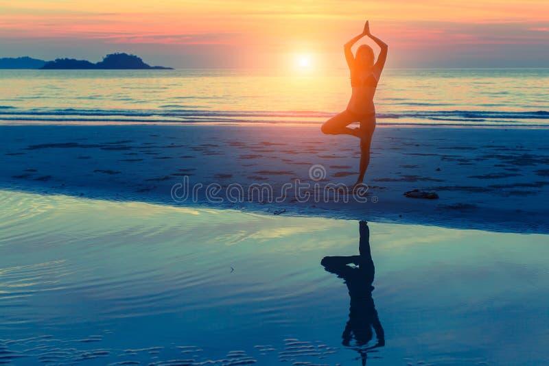 Yoga de pratique de femme sur la plage au coucher du soleil nature photos libres de droits