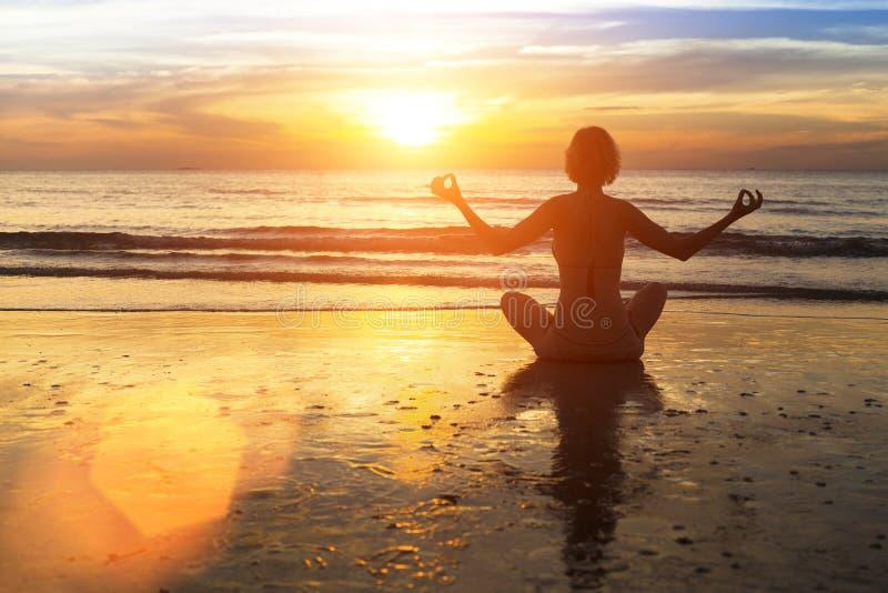 Yoga de pratique de femme sur la plage dans la lueur d'un coucher du soleil étonnant photo libre de droits