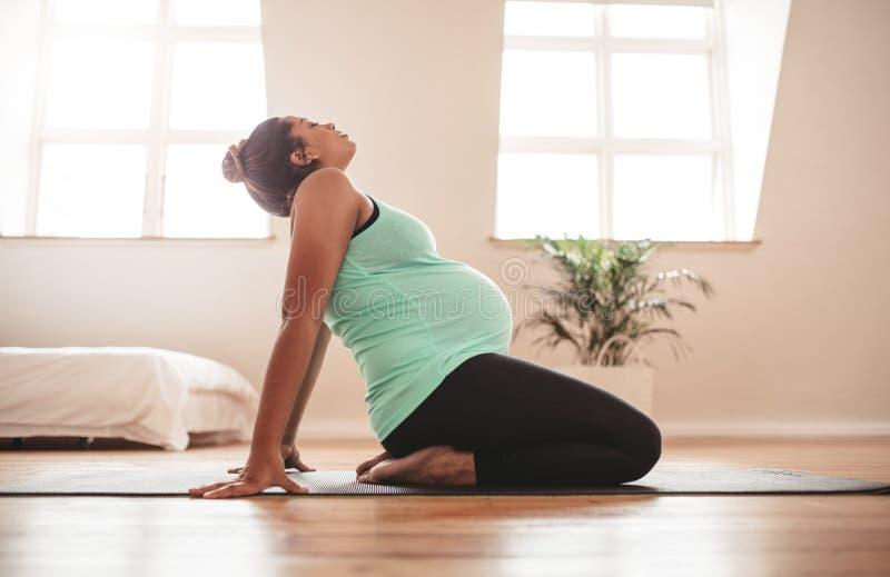 Yoga de pratique de grossesse de femme dans l'expectative à la maison images stock