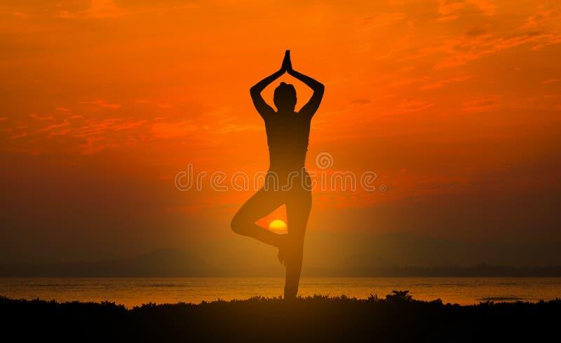 Yoga de pratique de jeune femme de silhouette sur la plage photographie stock
