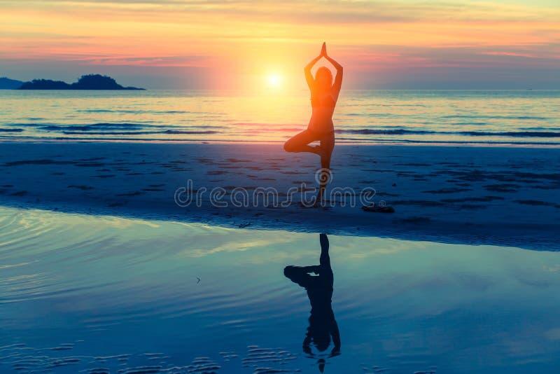 Yoga de pratique de jeune femme sur la plage au coucher du soleil avec la réflexion dans l'eau images libres de droits